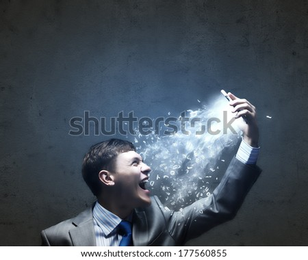 Angry businessman screaming furiously in to mobile phone - stock photo