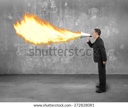Angry businessman screaming into megaphone spitting fire flame with concrete indoor background - stock photo