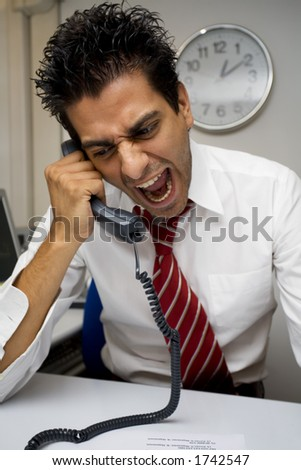 angry businessman screaming on the phone - stock photo