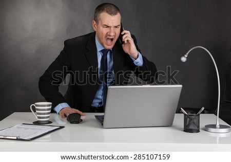 Angry businessman screaming on the phone. - stock photo