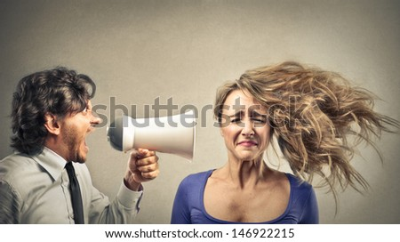 angry businessman screaming with megaphone to a woman - stock photo