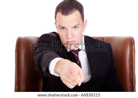 Angry businessman seated on a chair, pointing, isolated on white background. Studio shot. - stock photo
