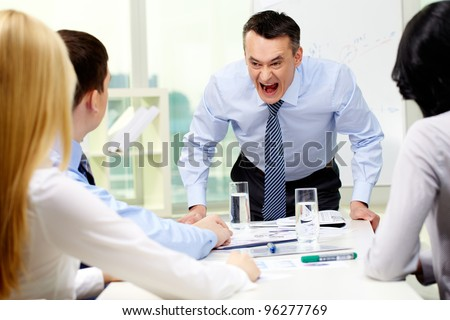 Angry businessman shouting at his workers with an expressive look - stock photo