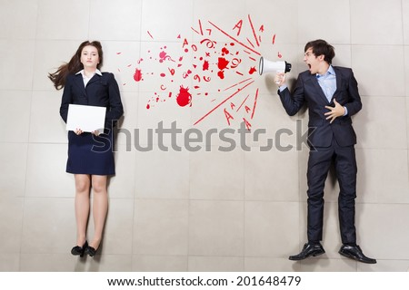 Angry businessman shouting in megaphone on his colleague - stock photo