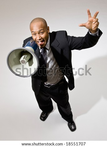 Angry businessman shouting instructions into megaphone