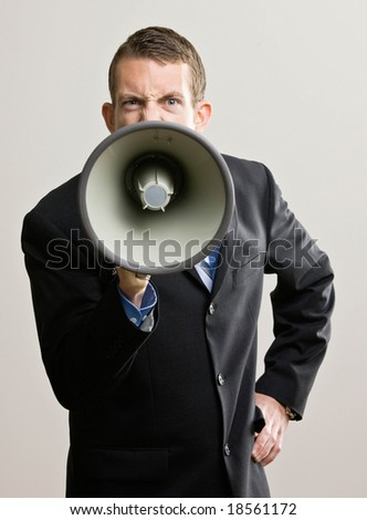Angry businessman shouting instructions into megaphone - stock photo