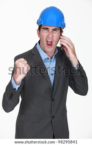 angry businessman shouting on his cell - stock photo