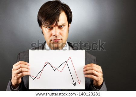 Angry businessman showing a falling graph of stock market against gray - stock photo
