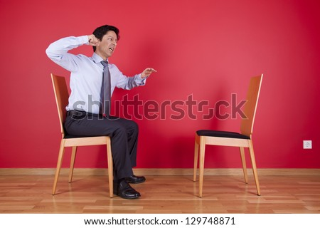 Angry businessman sited next to an empty chair - stock photo