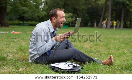 Angry businessman sitting on a grass with laptop. - stock photo