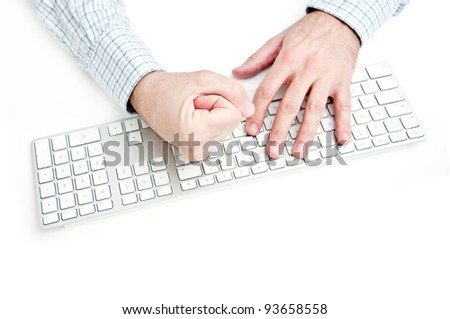 Angry businessman smashing computer keyboard on white desk top.
