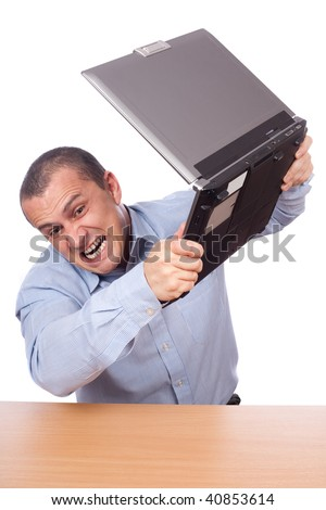 Angry businessman smashing his laptop on the table - stock photo