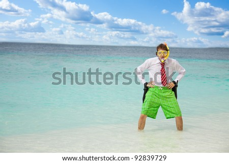 Angry businessman standing in the water on the beach with flippers - stock photo
