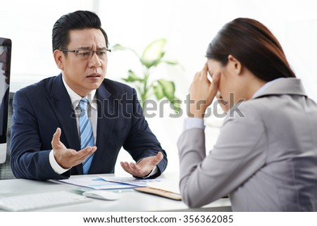 Angry businessman talking to his crying female assistant - stock photo