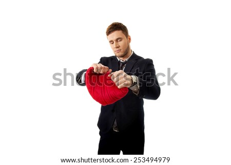 Angry businessman tears heart shaped pillow.