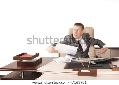 Angry businessman throwing papers in his office