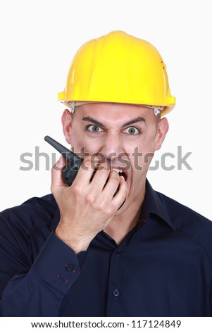 angry businessman wearing helmet and shouting on a walkie talkie - stock photo