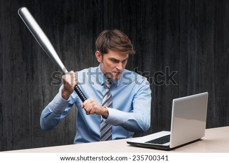 Angry businessman with laptop and bat - stock photo