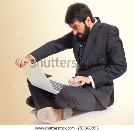 Angry businessman with laptop over ocher background - stock photo