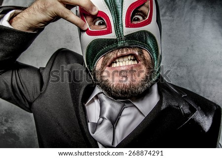 angry businessman  with Mexican wrestler mask - stock photo