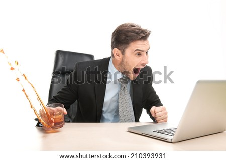 Angry businessman working at his laptop computer. man sitting on chair with glass and drinking alcohol - stock photo