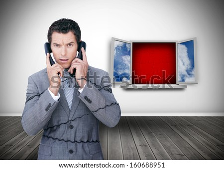 Angry businessman wrapped in cables phoning in front of open window - stock photo