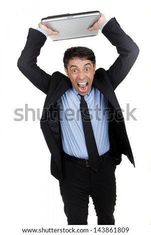Angry businessman yelling with a ferocious expression and open mouth standing with his arms raised throwing his laptop isolated on white - stock photo