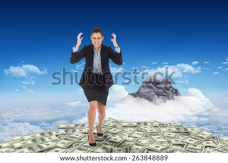 Angry businesswoman gesturing against mountain peak through clouds - stock photo