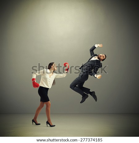 angry businesswoman in red boxing gloves punching businessman over dark grey background - stock photo