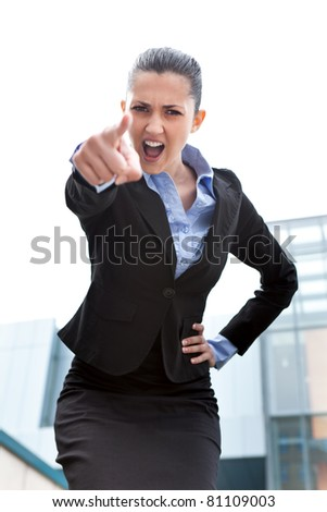angry businesswoman looking and pointing upset at camera, standing outdoor front office building - stock photo