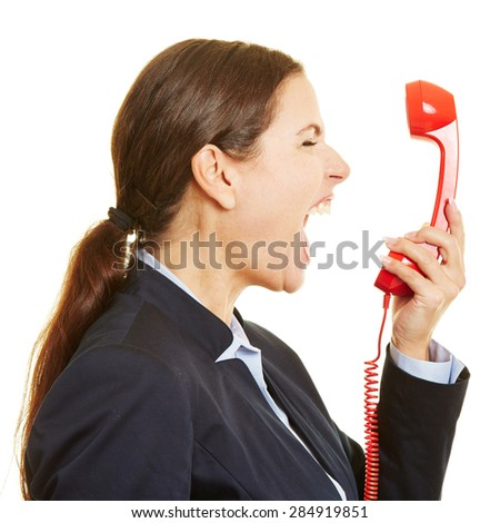 Angry businesswoman screaming loudly into a red phone - stock photo
