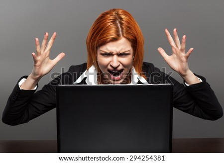 Angry Businesswoman screams at the laptop - stock photo
