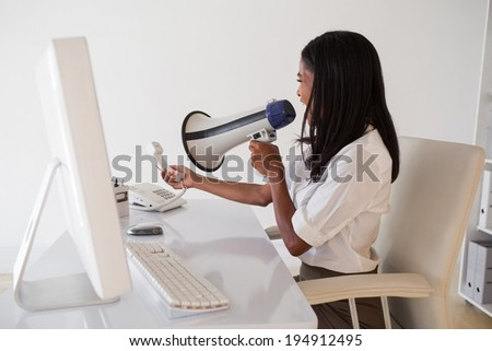 Angry businesswoman shouting in megaphone at phone in her office - stock photo