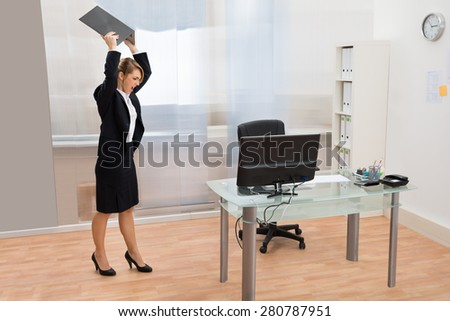 Angry Businesswoman Standing At Desk Throwing Laptop In Office - stock photo