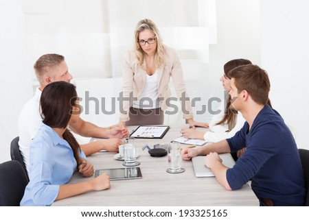 Angry businesswoman standing at office desk with colleagues in meeting