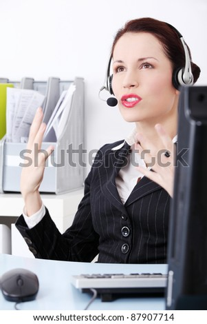 Angry  businesswoman talking by headset.