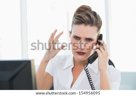 Angry businesswoman talking on the phone in her office - stock photo