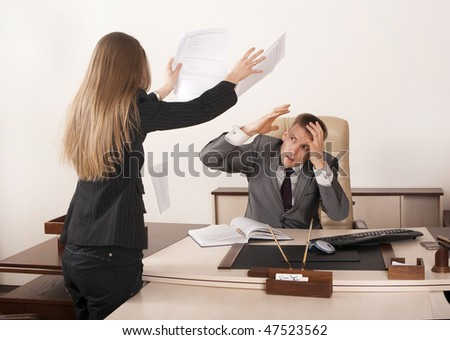 Angry businesswoman throwing papers in her boss