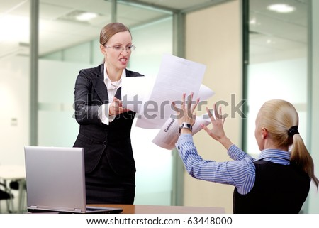 Angry businesswoman throwing papers in her partner - stock photo