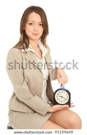 Angry businesswoman with alarm clock - stock photo