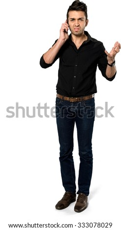 Angry Caucasian man with short black hair in casual outfit using mobile phone - Isolated