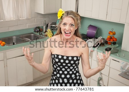 Angry Caucasian woman screams in her kitchen - stock photo