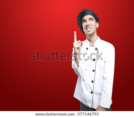 Angry chef pointing up - stock photo