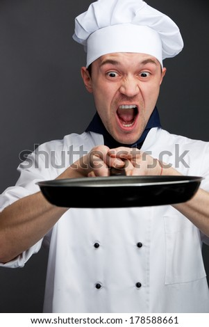 Angry chief in uniform holding pan isolated on grey - stock photo