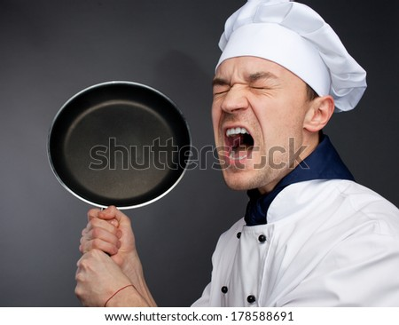 Angry chief in uniform threaten by pan isolated on grey - stock photo