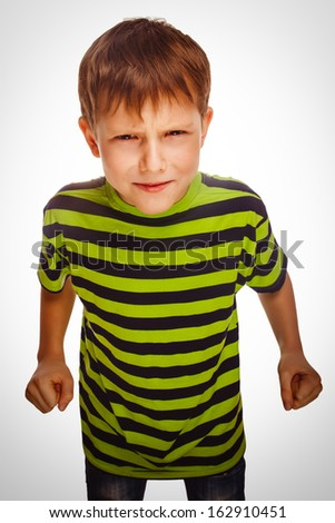 angry child boy blond bully bad aggressive fights in striped green shirt - stock photo