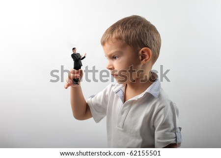 Angry child holding a scared businessman - stock photo