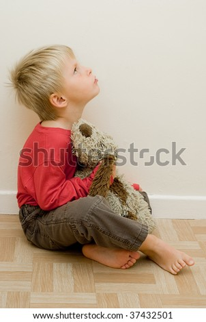 angry child looks upwards holding his toy dog.