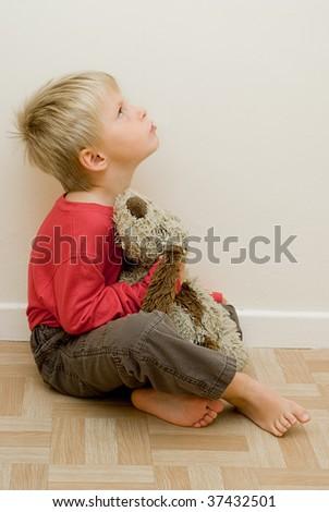 angry child looks upwards holding his toy dog. - stock photo