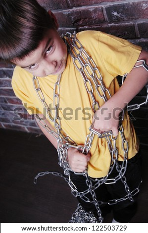 Angry child prisoner with chain trying to pull it off - stock photo